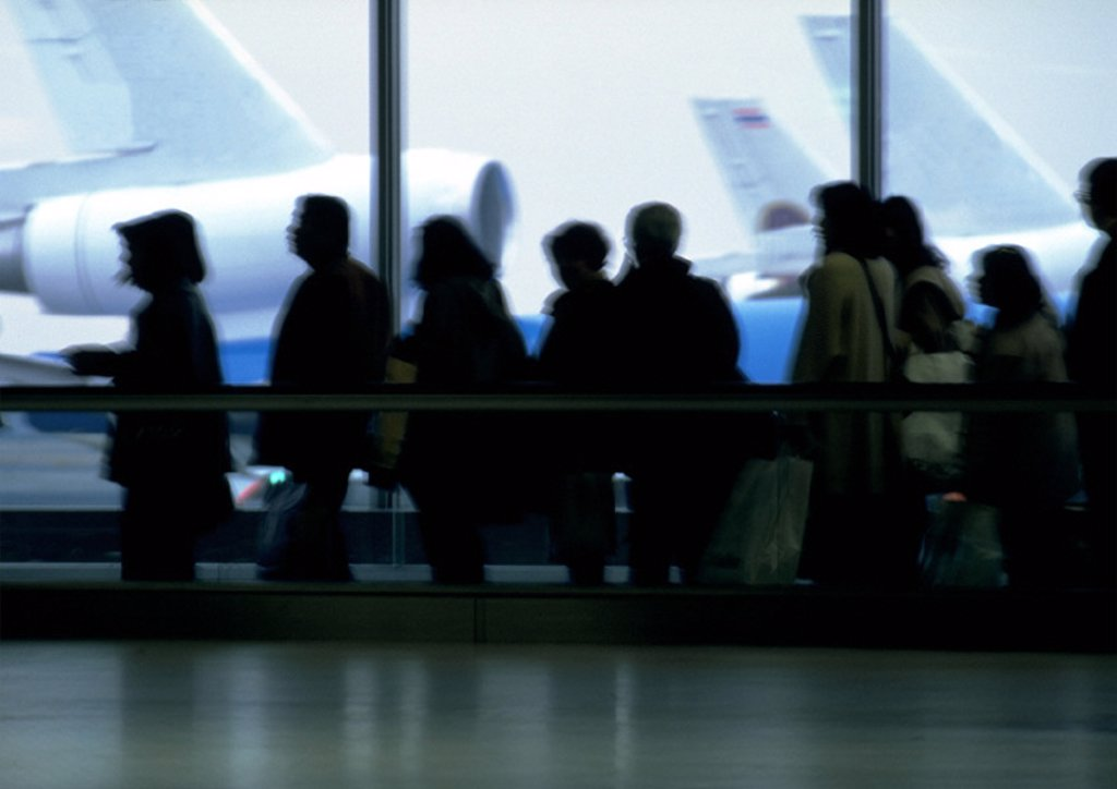 Crowd in airport on moving walkway, blurred : Stock Photo