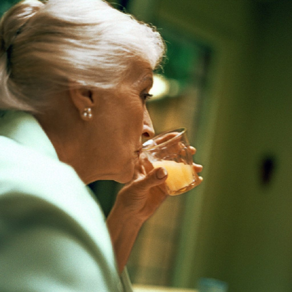 Mature woman drinking, close-up : Stock Photo