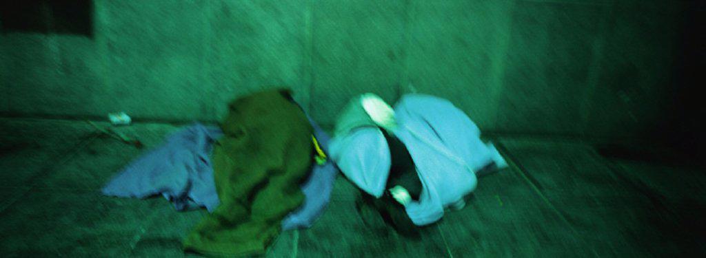 Stock Photo: 1569R-146040 Homeless people sleeping on sidewalk, blurred