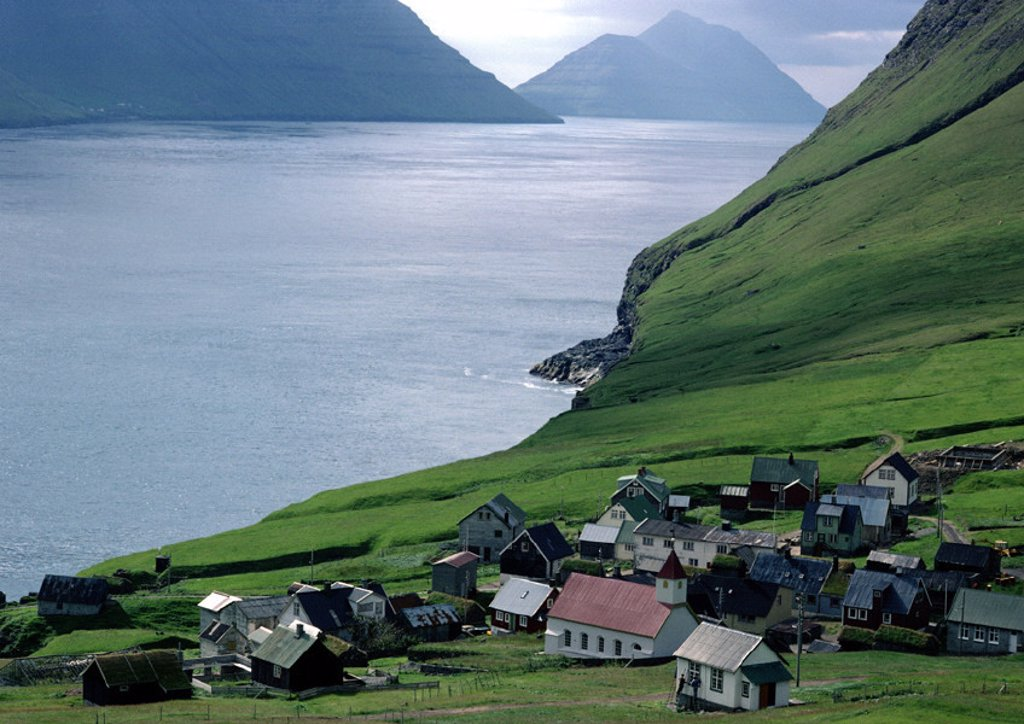Scandinavia, village overlooking sea with mountains in background : Stock Photo