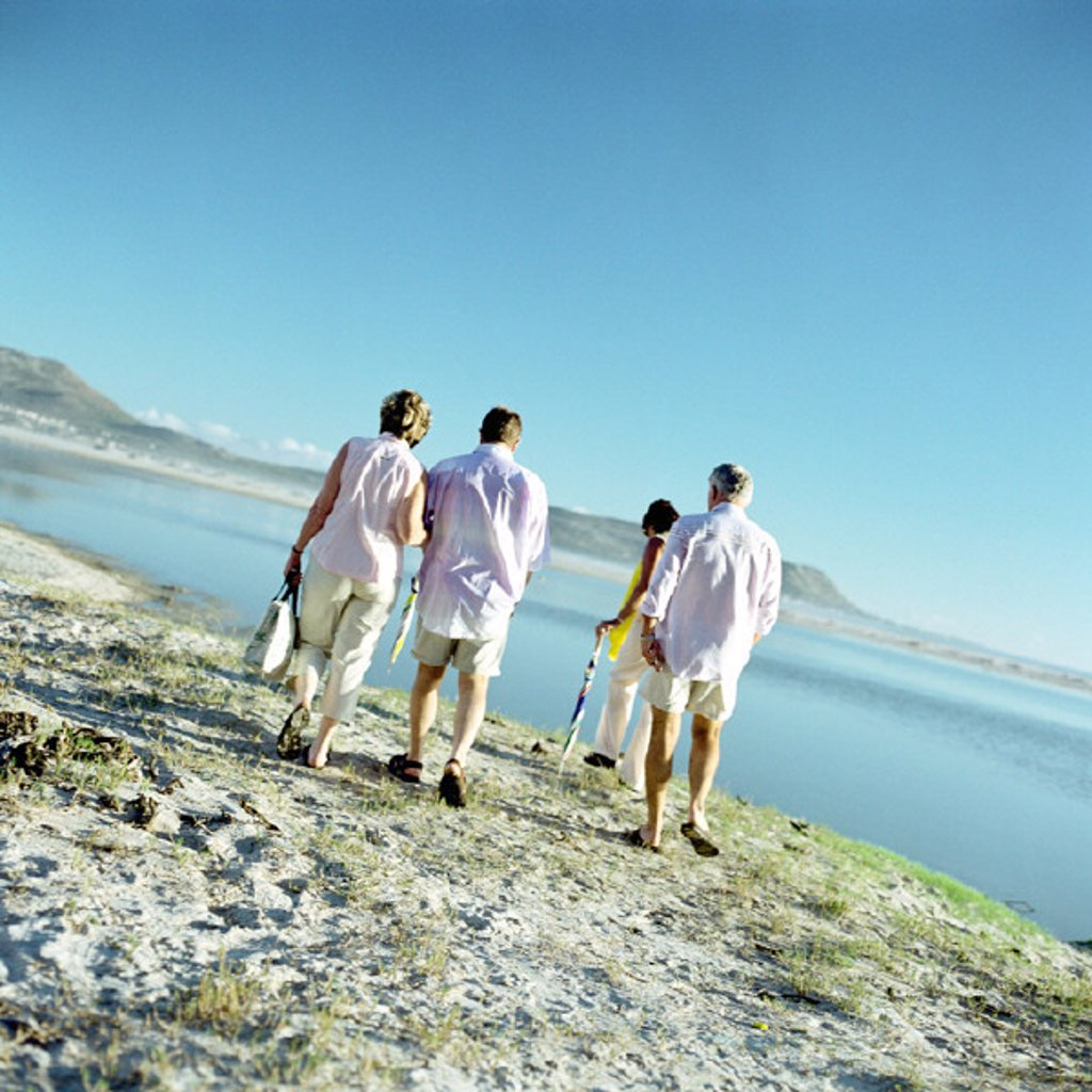 Two mature couples walking by the sea, rear view : Stock Photo
