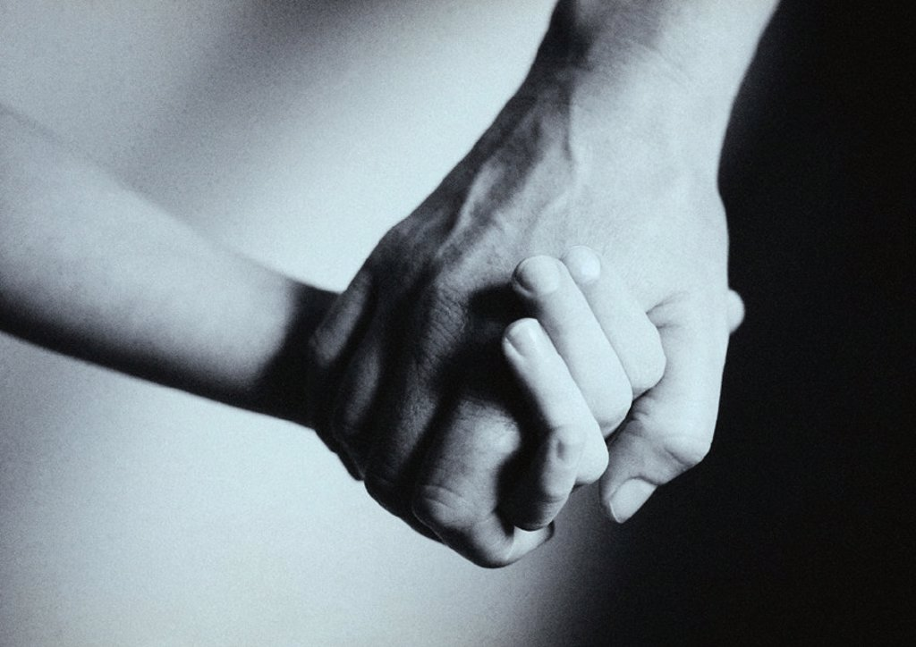 Stock Photo: 1569R-154002 Man and child holding hands, close-up, b&w