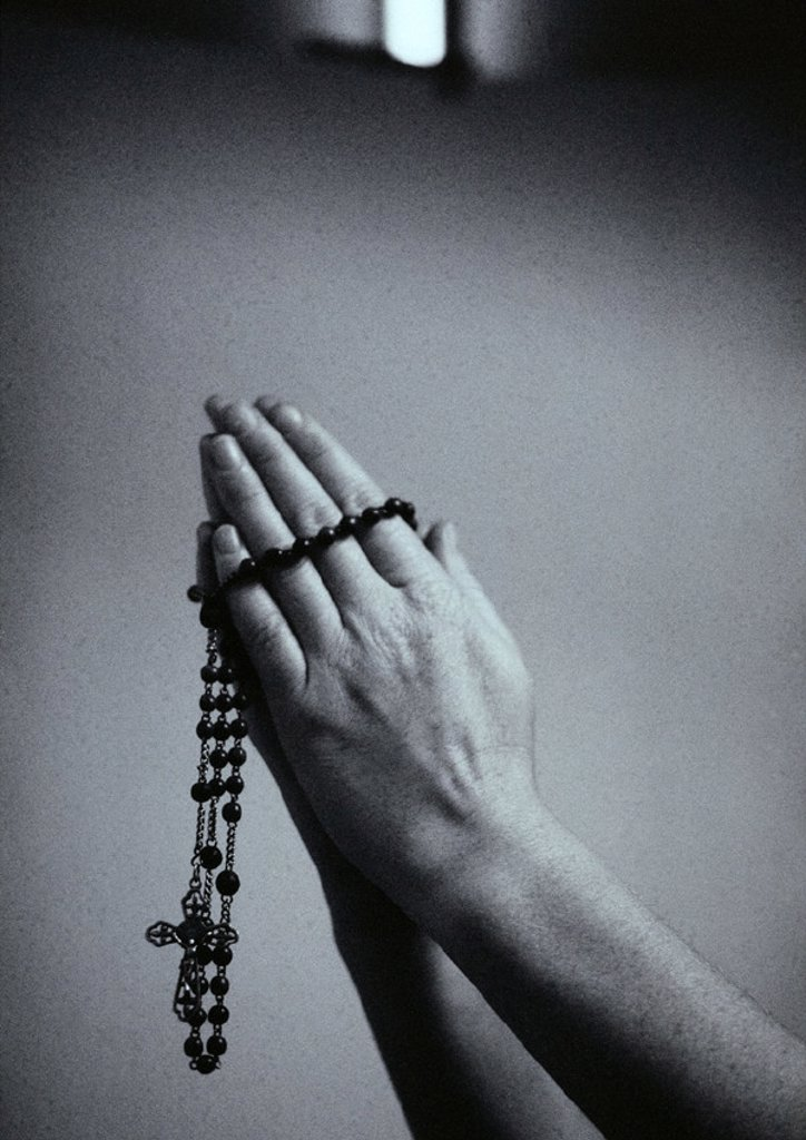 Stock Photo: 1569R-154022 Hands holding rosary beads, b&w