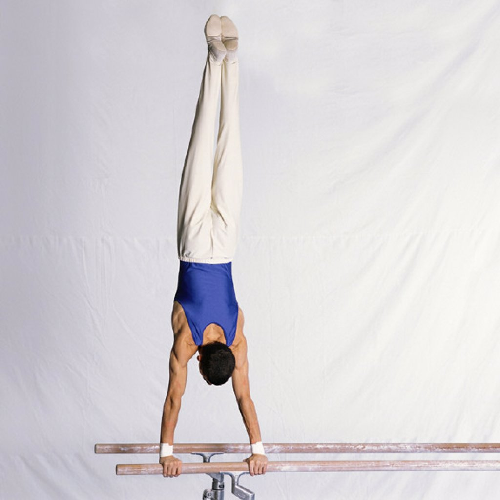 Stock Photo: 1569R-155012 Young male gymnast performing routine on parallel bars