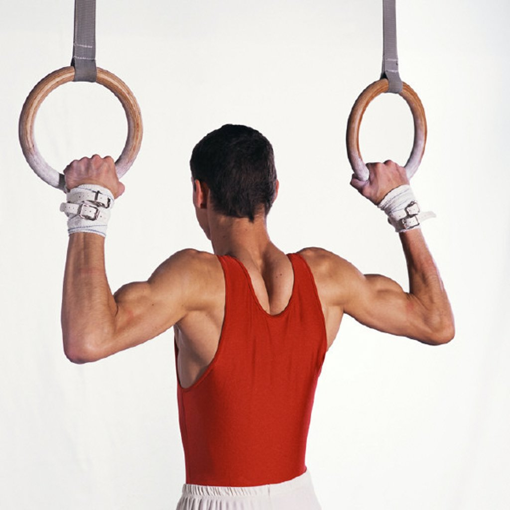 Stock Photo: 1569R-155017 Male gymnast pulling himself up on rings, upper section, rear view