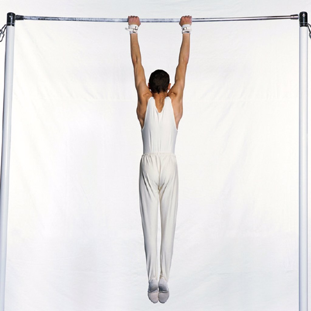 Male gymnast on horizontal bar, rear view : Stock Photo