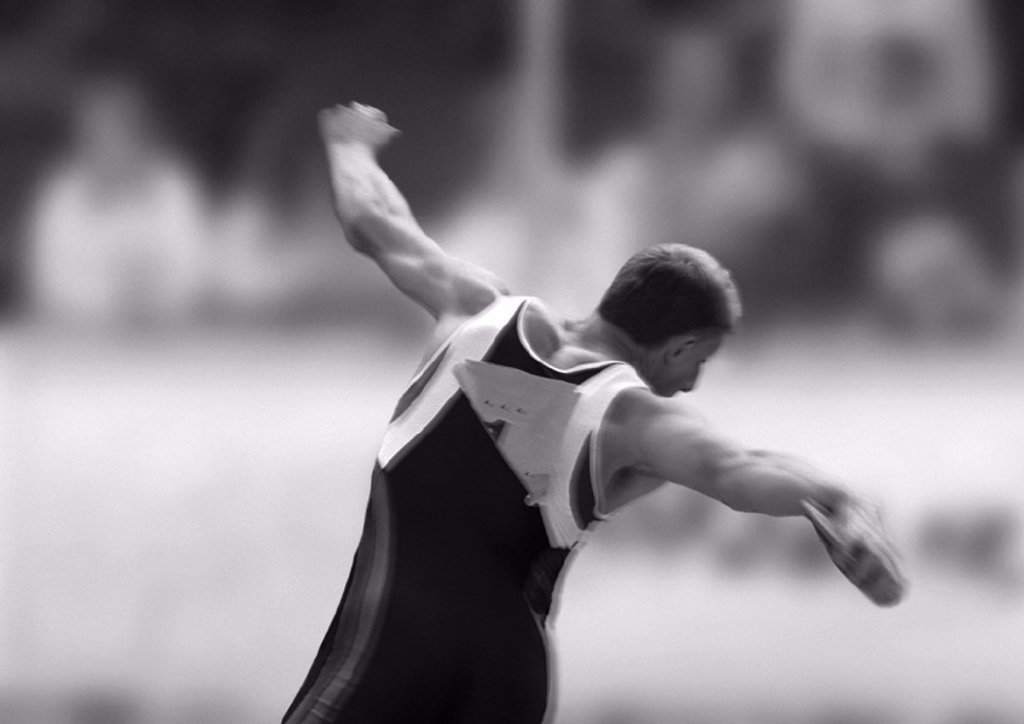 Stock Photo: 1569R-156021 Male athlete throwing discus, rear view, b&w