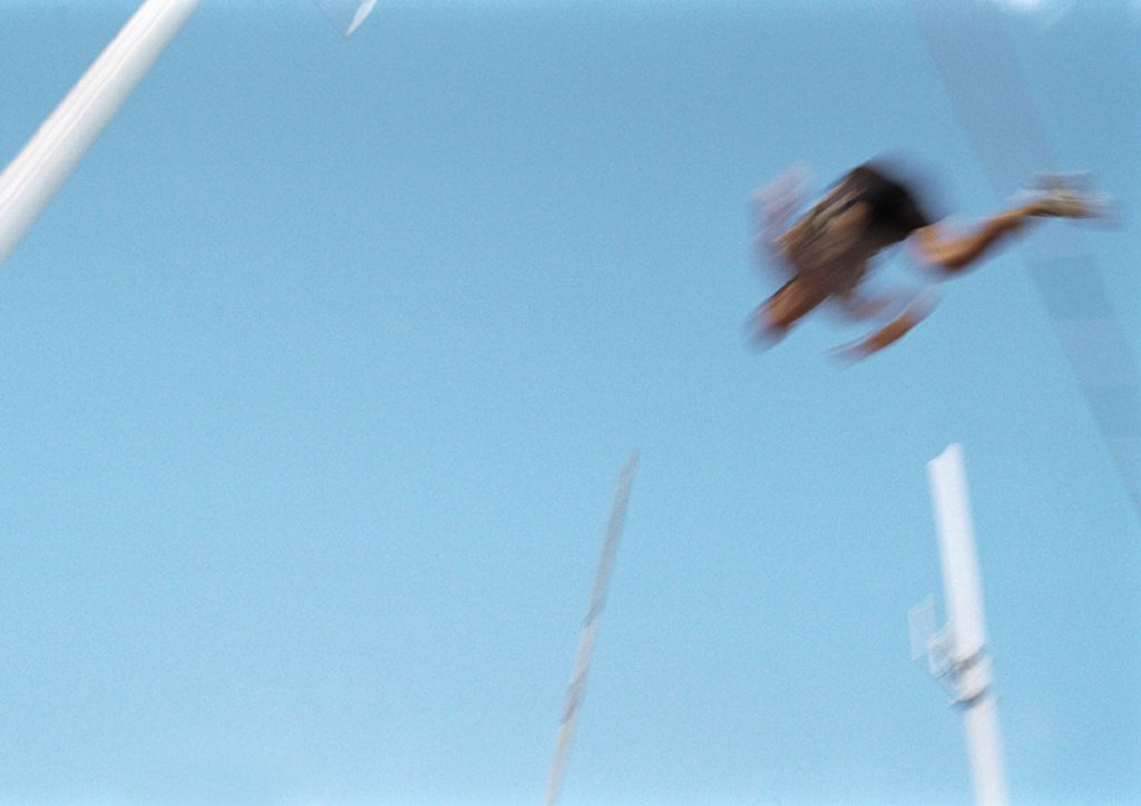 Male pole vaulter in mid-air, blurred motion : Stock Photo