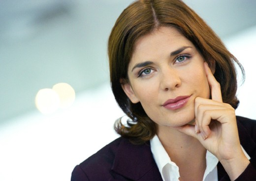 Woman looking into camera, hand on cheek, portrait : Stock Photo