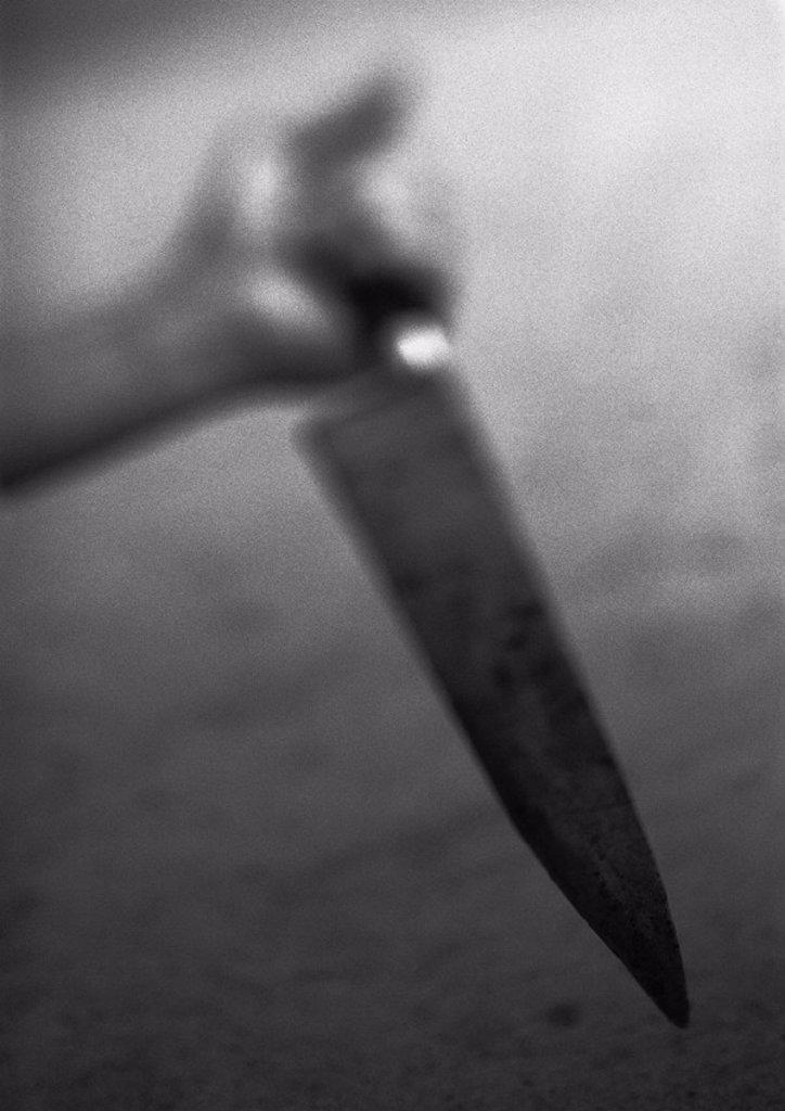 Stock Photo: 1569R-158063 Hand holding kitchen knife, blurred, b&w