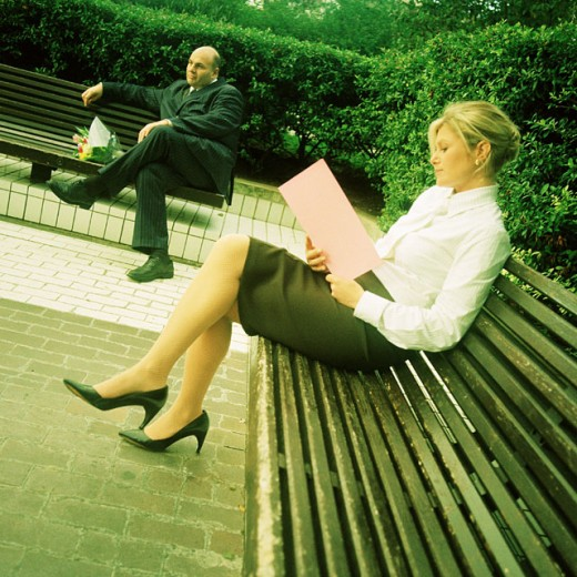 Two business people sitting on benches : Stock Photo