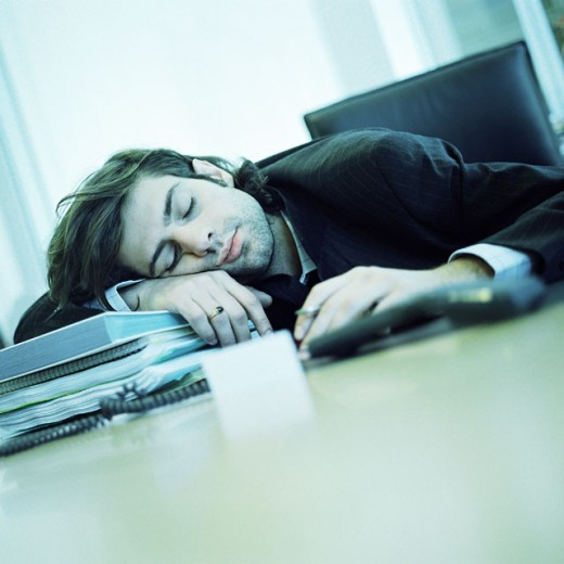 Young businessman sleeping at desk : Stock Photo