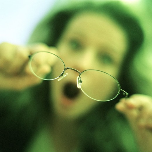 Woman holding glasses, focus on glasses in foreground : Stock Photo