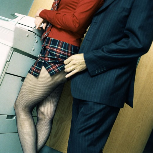 Woman standing at photocopy machine, man in suit lifting woman´s skirt, mid-section : Stock Photo