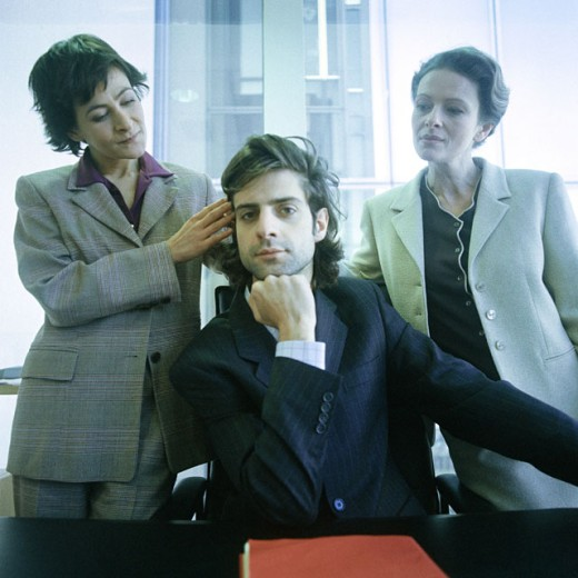 Young man looking into camera, two women behind him, one touching his hair : Stock Photo