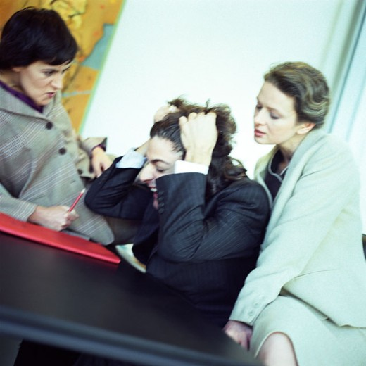 Man in suit pulling his hair, two women watching, portrait : Stock Photo