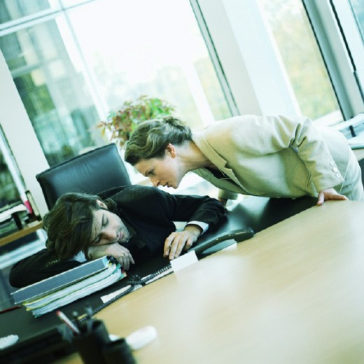 Young woman watching colleague sleeping at desk : Stock Photo