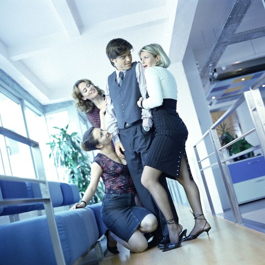 Three young women office workers surrounding male colleague : Stock Photo