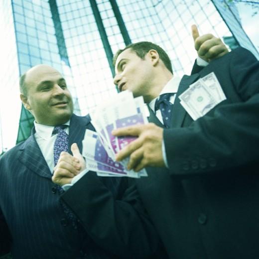 Two businessmen, one holding handfull of bills, portrait : Stock Photo