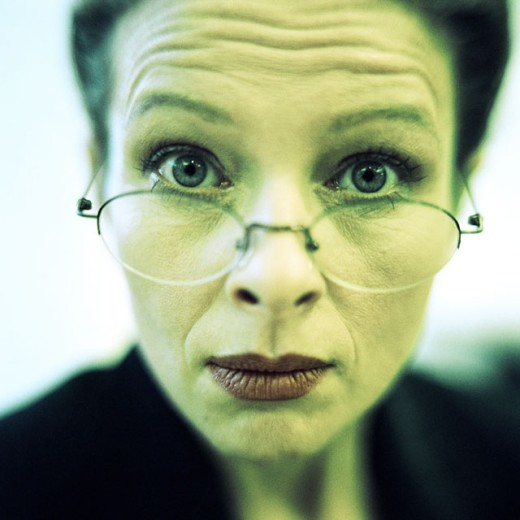Close-up of businesswoman wearing glasses, raising eyebrows, close-up : Stock Photo