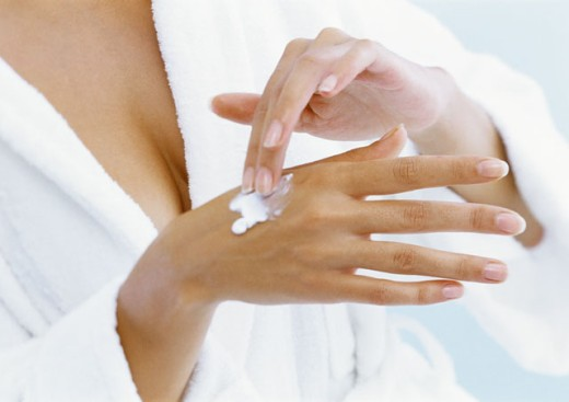 Woman applying moisturizer to hand, close-up : Stock Photo