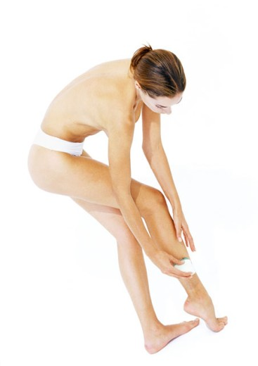 Woman shaving legs, semi-nude, side view : Stock Photo