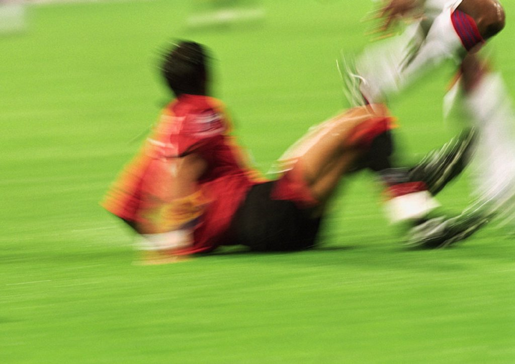 Two soccer players in match, one on field, blurred : Stock Photo