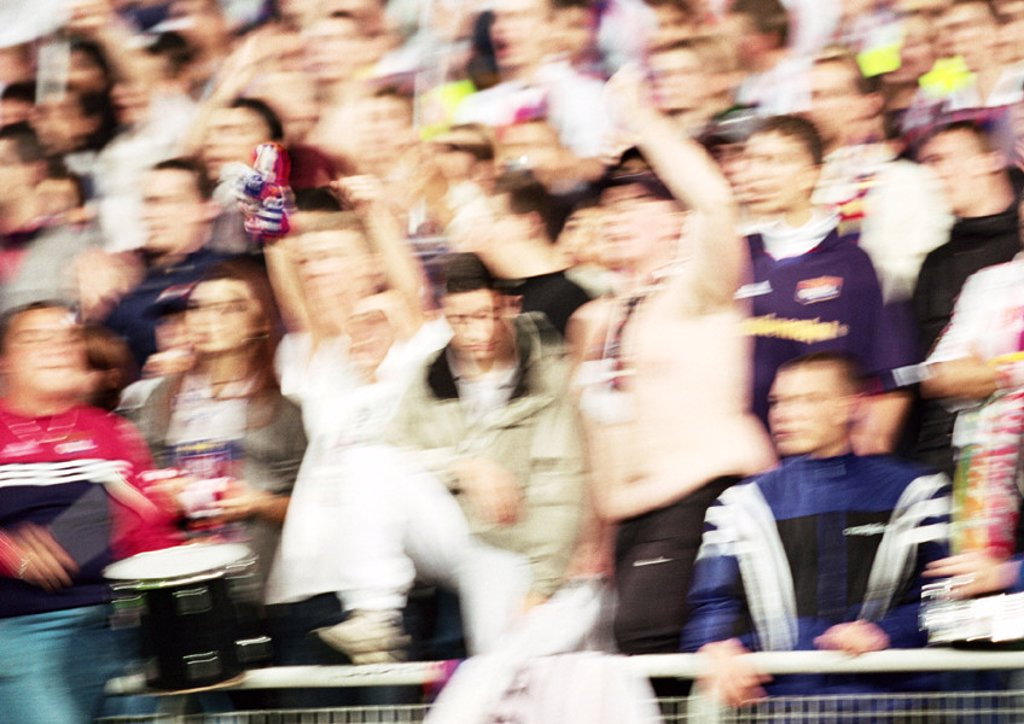 Soccer fans at a match, blurred : Stock Photo