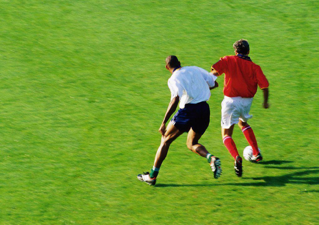 Stock Photo: 1569R-164045 Two soccer players running for ball, full length