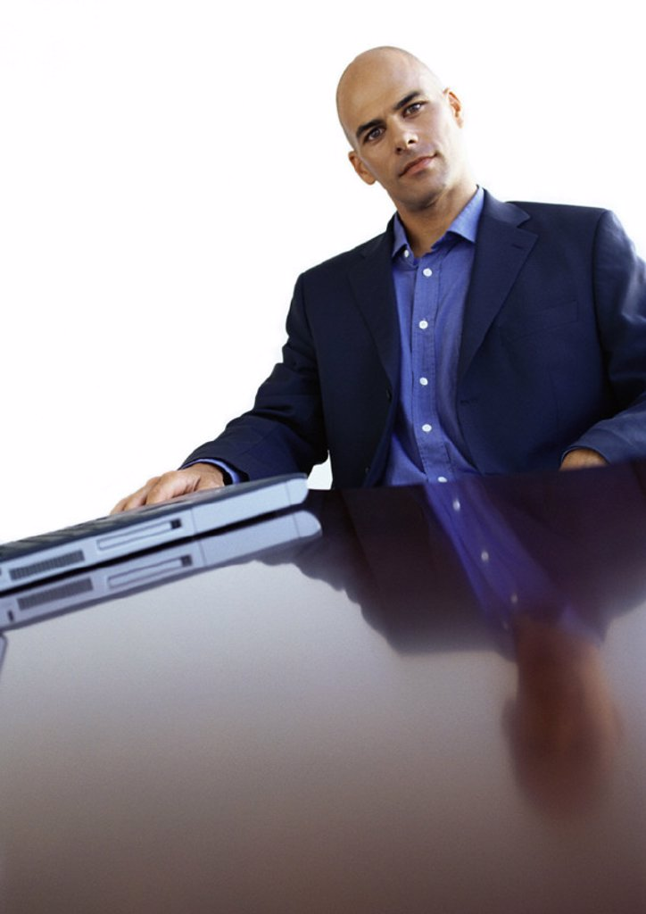 Businessman sitting at desk, portrait : Stock Photo