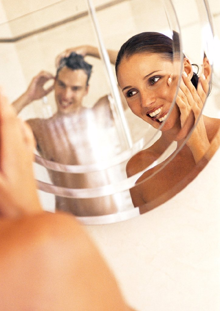 Couple looking at each other in mirror in bathroom : Stock Photo