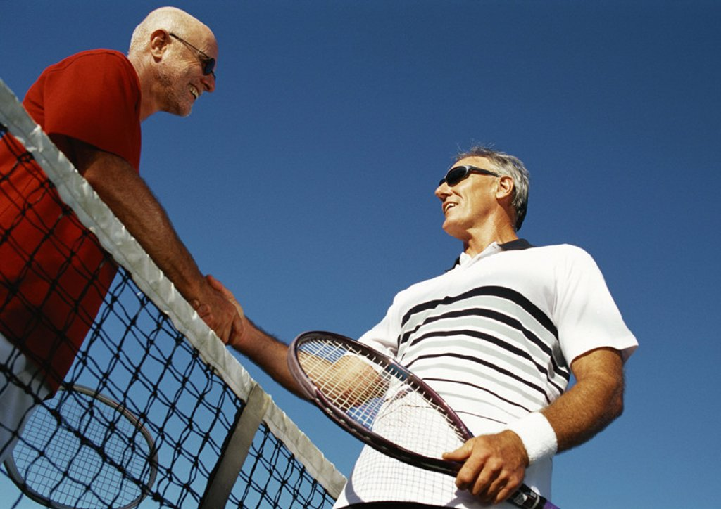 Stock Photo: 1569R-175001 Two mature men shaking hands over tennis net, low angle view
