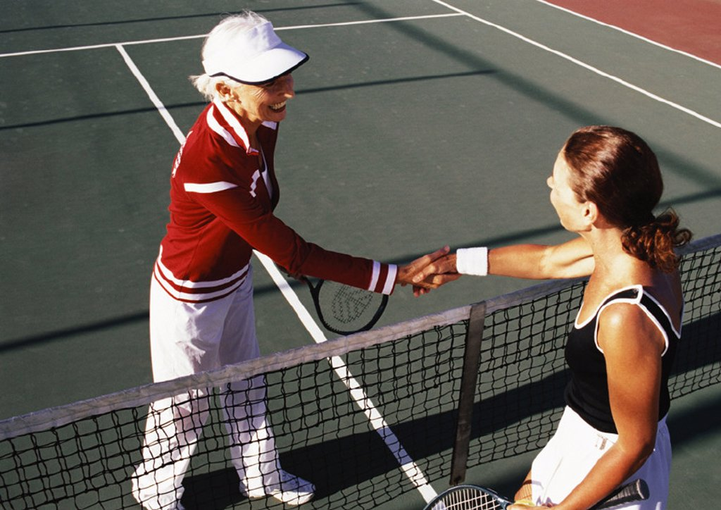 Two mature women shaking hands on tennis court : Stock Photo