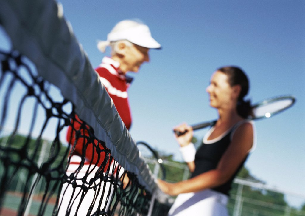 Two mature women talking on tennis court, blurred : Stock Photo