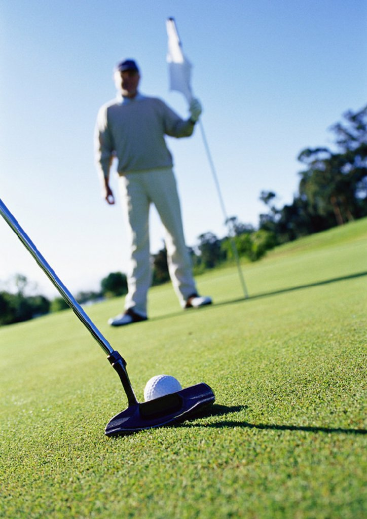 Golfer holding flag on green, putter and ball in foreground : Stock Photo