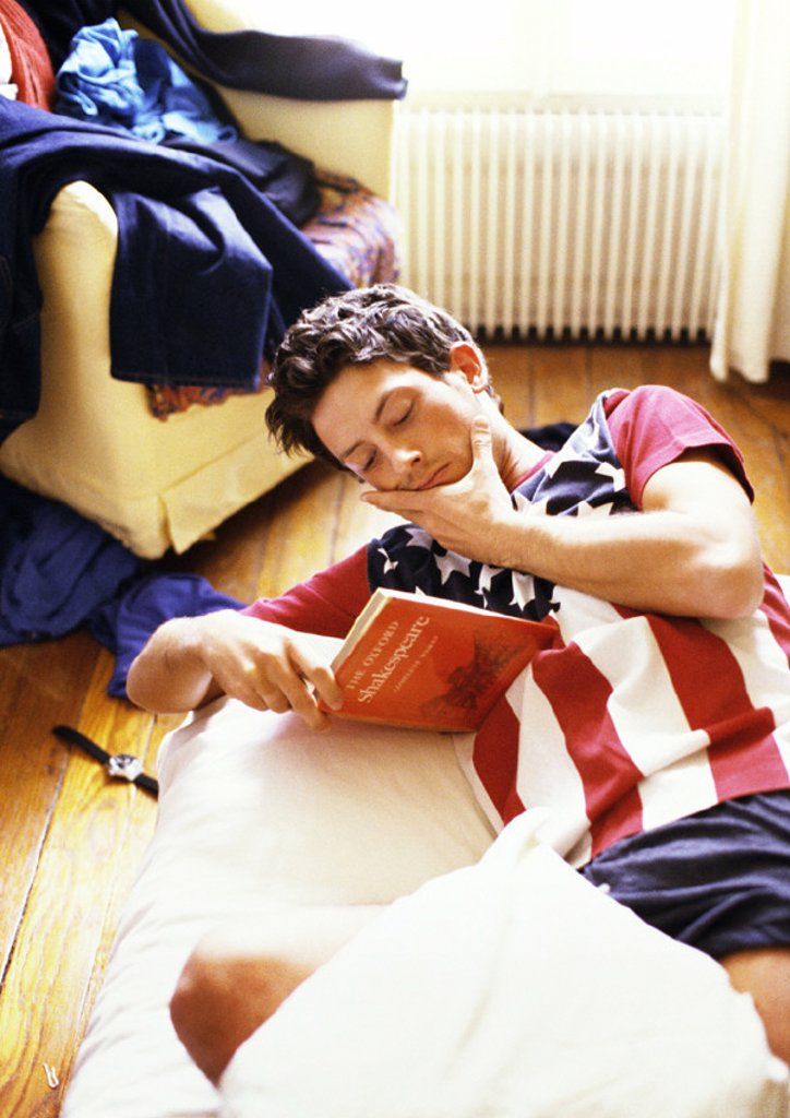 Stock Photo: 1569R-179006 Man reading book on bed