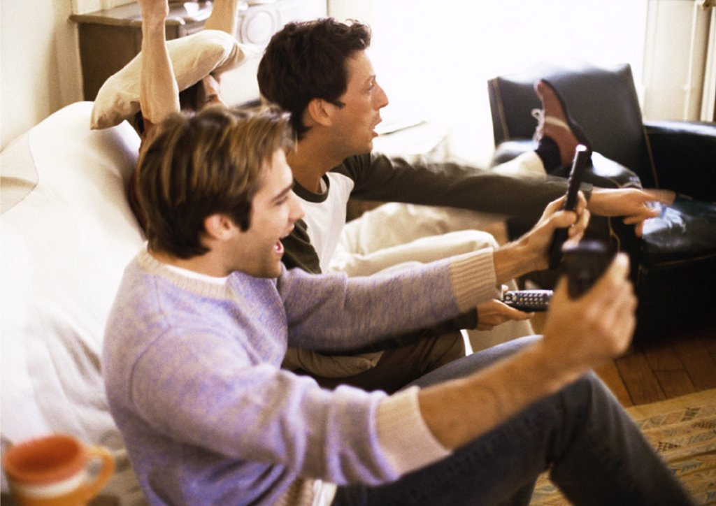 Three men sitting on sofa, gesturing, side view : Stock Photo