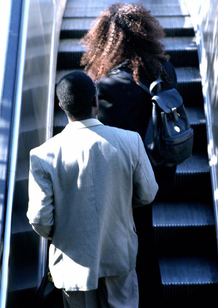 Stock Photo: 1569R-18023 Couple riding escalator, rear view