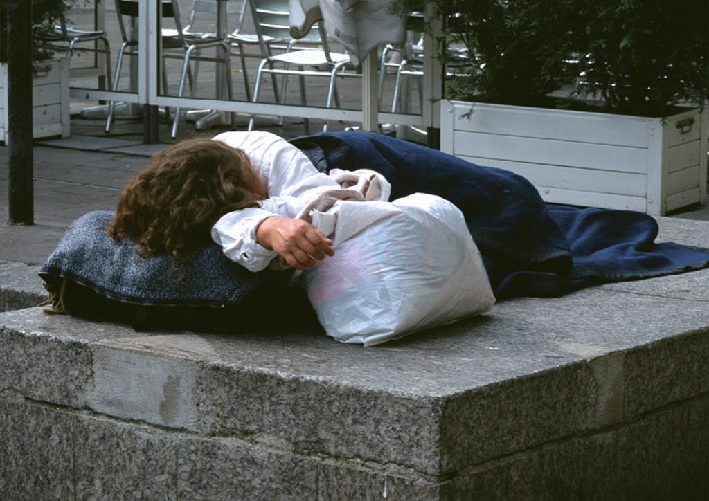 Stock Photo: 1569R-18072 Person sleeping on sidewalk near café