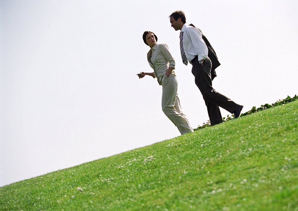 Businessman and woman walking on grass : Stock Photo