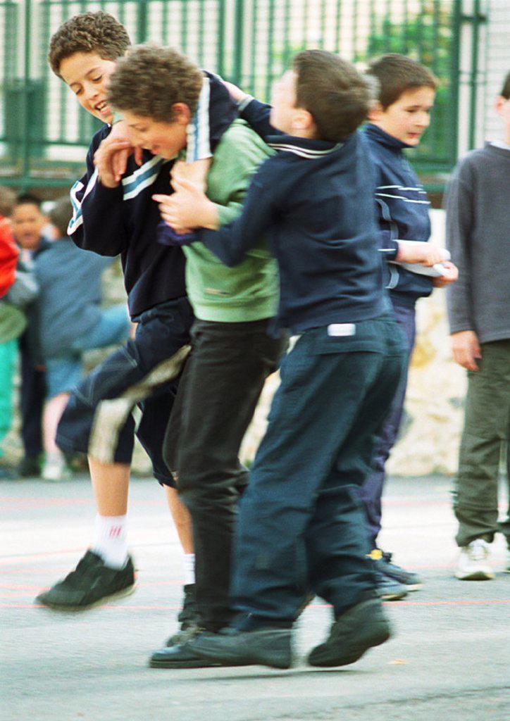 Children playfighting in schoolyard : Stock Photo