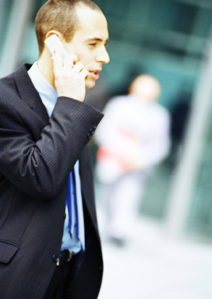 Stock Photo: 1569R-187023 Businessman using cell phone, side view