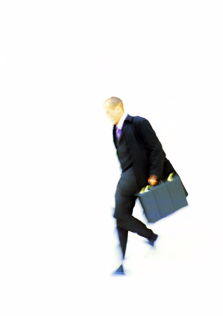Stock Photo: 1569R-187053 Businessman walking with briefcase in hand, elevated view