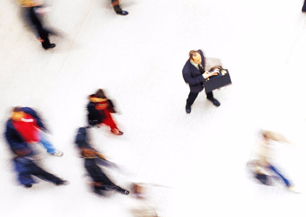 Businessman in crowd, elevated view, blurred : Stock Photo