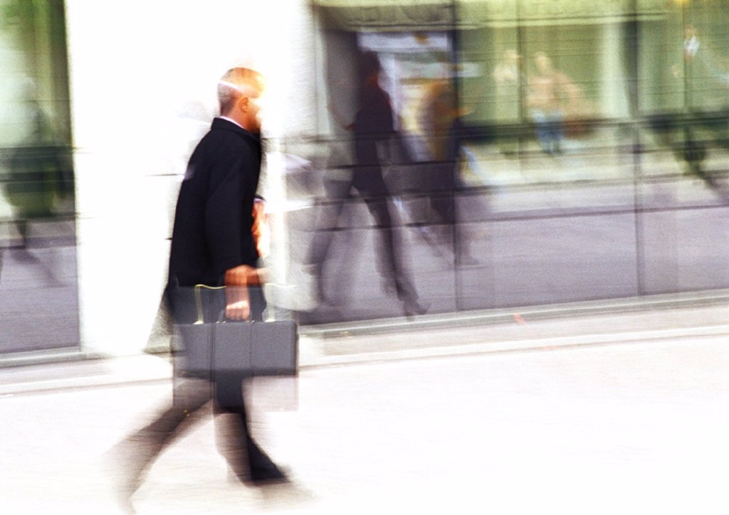 Businessman holding briefcase, blurred : Stock Photo