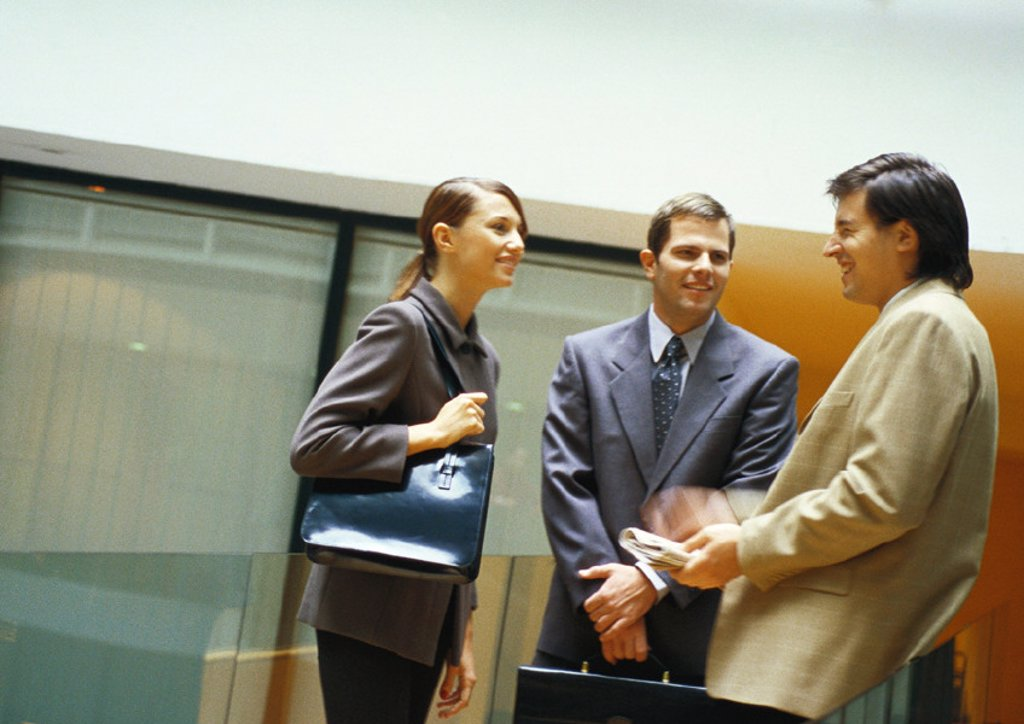 Three businesspeople standing and talking : Stock Photo