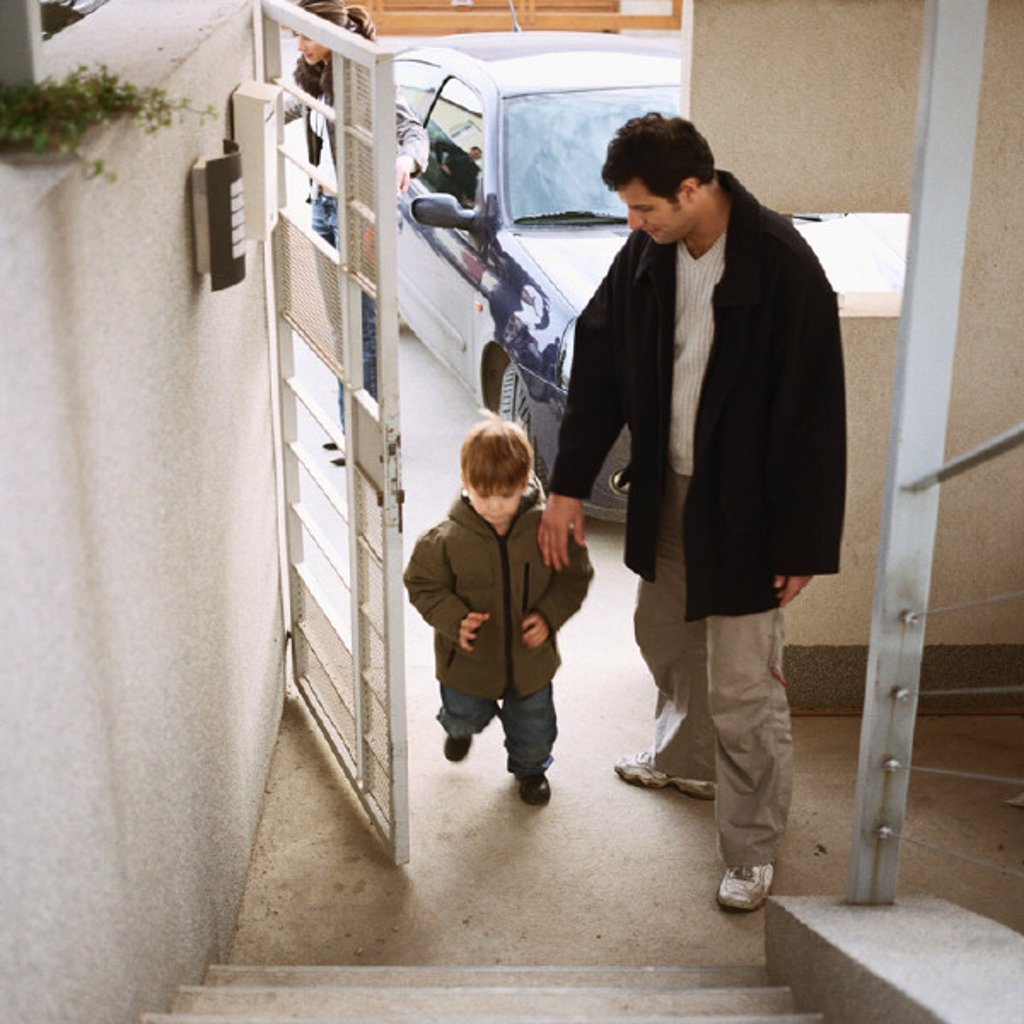 Father coming in door with with son, full length, high angle view : Stock Photo