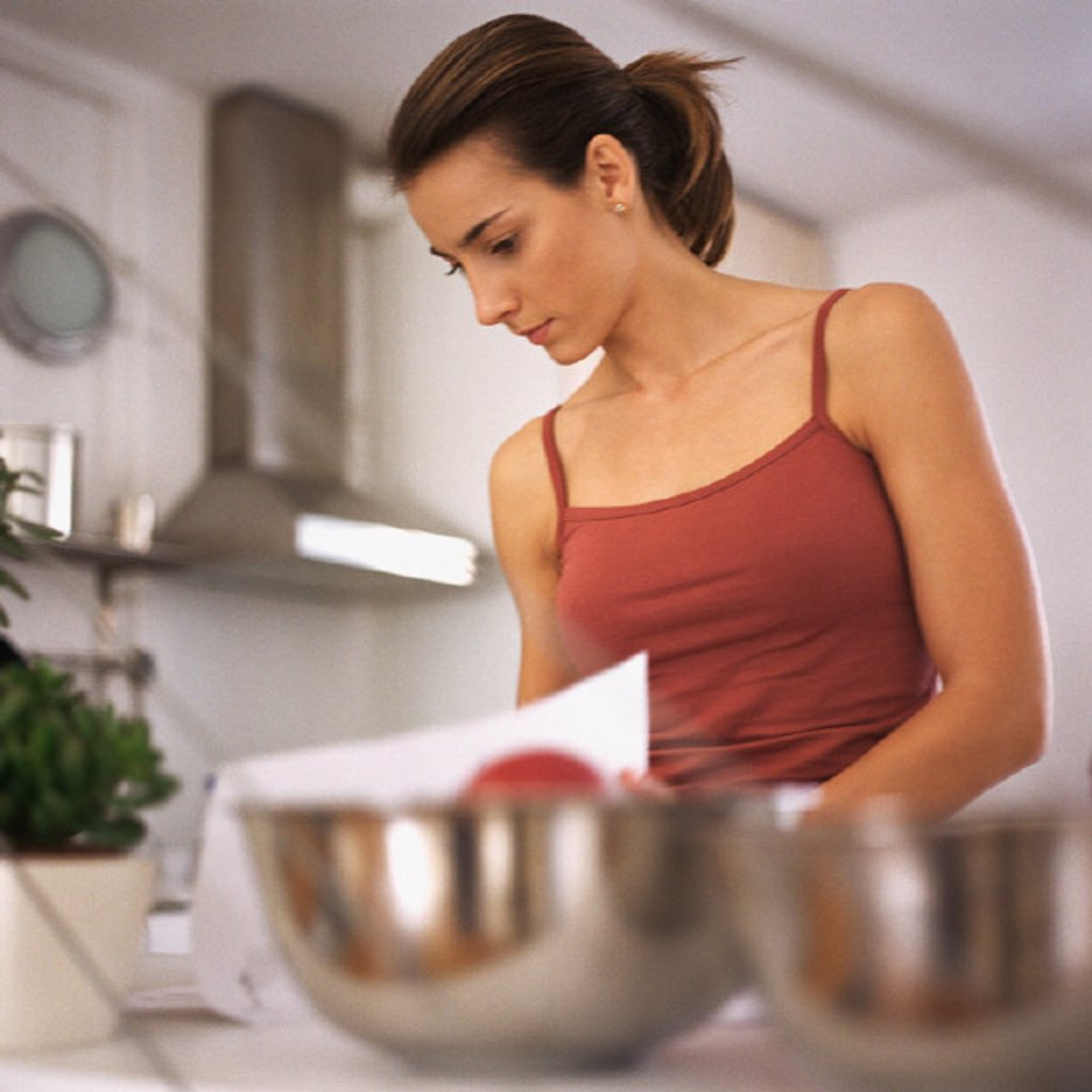 Woman working in kitchen, waist up, bowls on counter in foreground, blurred : Stock Photo