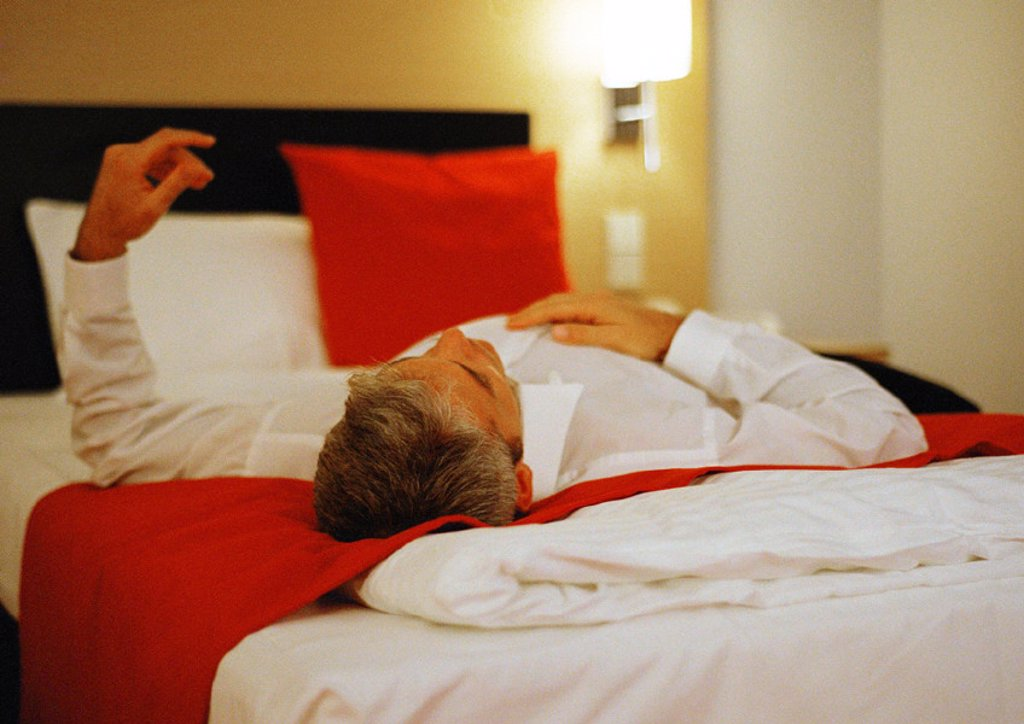Businessman lying across bed : Stock Photo