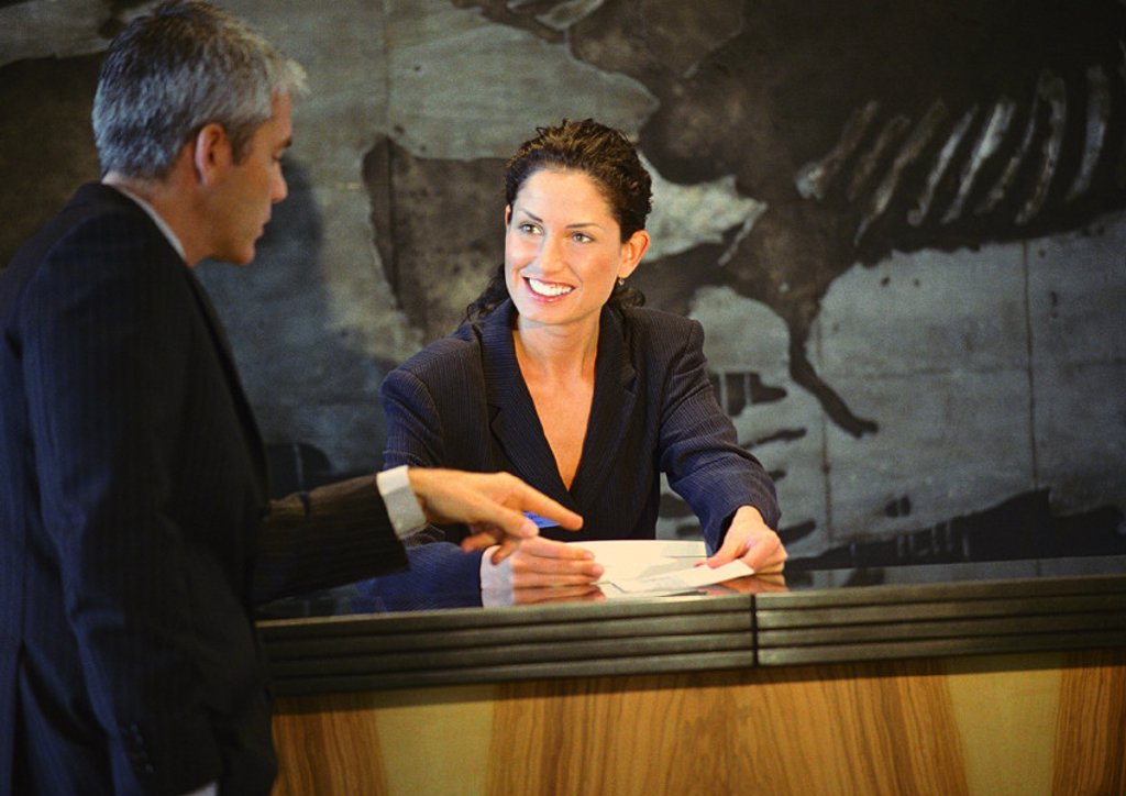 Man standing in front of woman at counter, man pointing to paper in woman´s hands : Stock Photo
